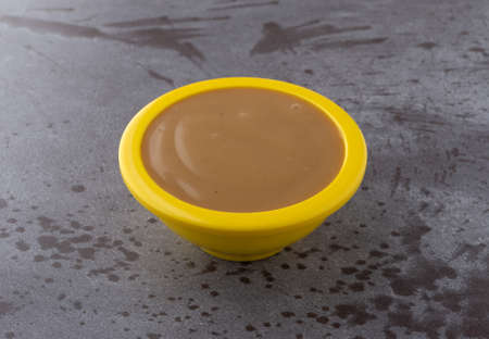 Side view of creamy brown turkey gravy in a small yellow bowl on a gray background.