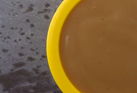 Overhead close view of brown turkey gravy in a small yellow bowl on a gray background.