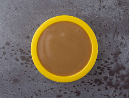 Overhead view of brown turkey gravy in a small yellow bowl on a gray background.