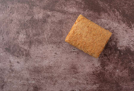 Overhead view of a blueberry fig bar offset on a maroon background illuminated with natural lighting.