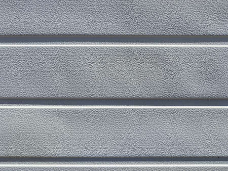 Rows of vinyl textured gray siding in the early morning light.