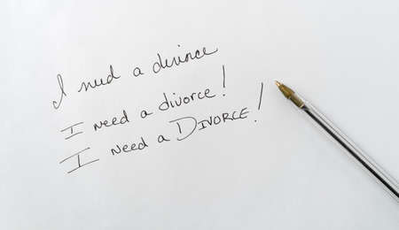 Top view of a note saying I need a divorce with an exclamation mark plus a pen to the side on white paper.
