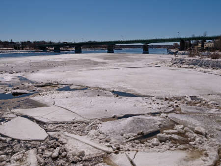 Ice flows large and small breaking up in the early spring on the Penobscot river in Maine with a long bridge in the background.