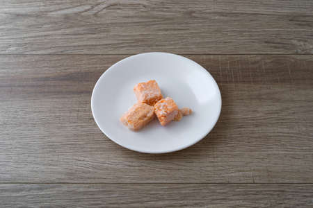 Tabletop view of pieces of salmon on a white plate illuminated with natural lighting.