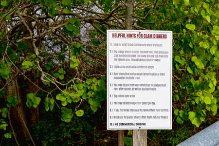 A public sign on how to dig clams near a guardrail on the coast of Maine. 免版税图像