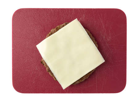 Single fried all beef lean hamburger patty with a slice of white American cheese on a red cutting board isolated on a white background.