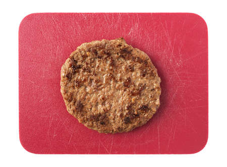 Single fried all beef lean hamburger patty on a red cutting board isolated on a white background.