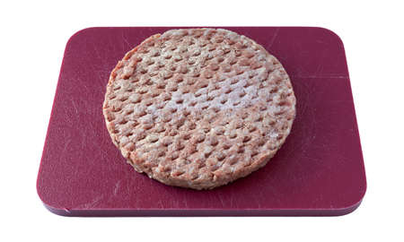 Side view of a frozen all beef lean hamburger patty atop a red cutting board isolated on a white background.