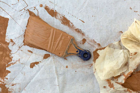 Close view of a painters drop cloth with brown paint covering a used brush and cloth rag to the side.