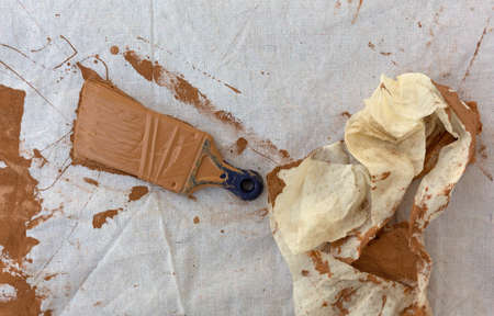 Painters drop cloth with brown paint covering a used brush and cloth rag to the side.