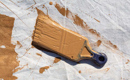 Painters drop cloth with brown paint covering a used brush. 免版税图像