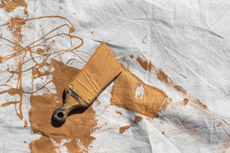 Painters drop cloth with brown paint covering a used brush. Imagens