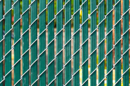 Close view of a chain link fence with green privacy slats.