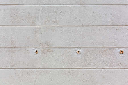 Rows of painted concrete blocks with weep holes.