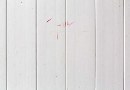 Close view of a dirty white plastic fence with streaks of red paint.