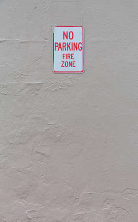 Concrete painted wall with a no parking fire zone sign.