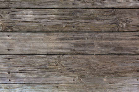 Several rows of old weathered wood decking with cracks and rot from the elements.