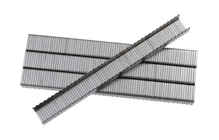 Several sections of industrial steel staples with one upside down on top isolated on a white background.