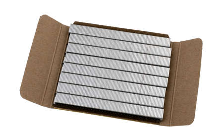 Several rows of industrial steel staples in an open cardboard box isolated on a white background. 版權商用圖片