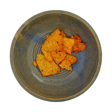 Top view of a bowl of broken cheese flavored tortilla chips isolated on a white background. Imagens