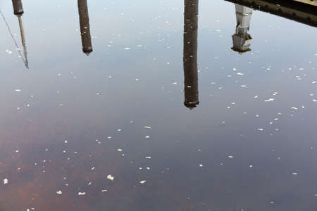 Reflection of a dock on the surface of water with foam on a cloudy day.