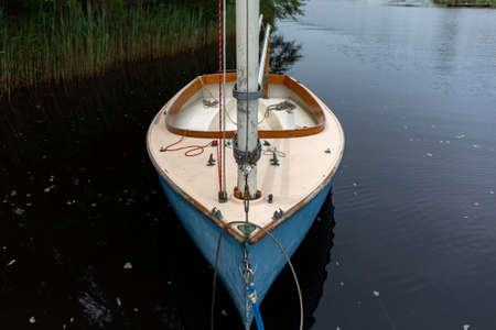 Close view of an old fiberglass sailboat anchored near the shore.