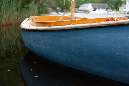 Close view of a small sailboat with a blue hull floating on a waterway with houses in the background. 版權商用圖片