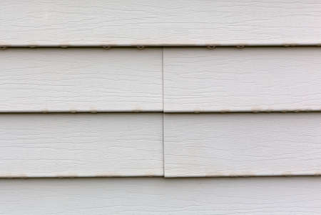 Wet vinyl siding with a joint in the center and water dripping from the bottom of the panels.