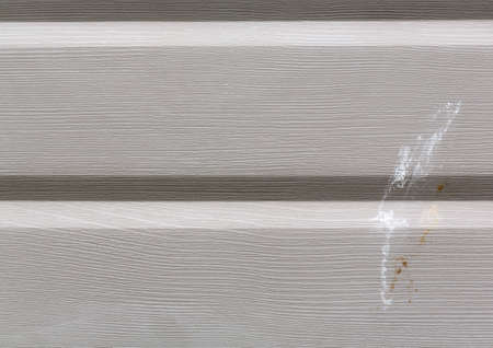 Close view of painted aluminum siding with bird droppings.