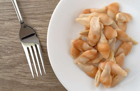 Top view of a serving of razor clams on a white plate with a fork to the side on a table illuminated with natural lighting.