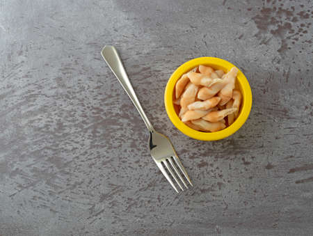 Top view of a small yellow bowl filled with razor clams plus a fork to the side on a gray table illuminated with natural lighting.