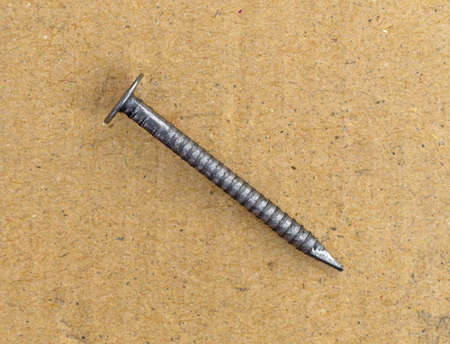 Top view of a single ring shank underlayment nail on a cardboard surface. Banco de Imagens