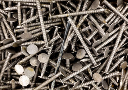 Top close view of ring shank underlayment nails with a black drill bit.