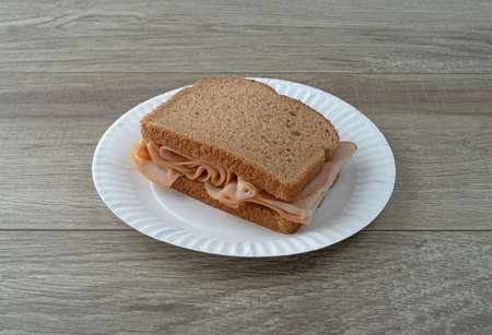 Sandwich with thin sliced smoked turkey on wheat bread on a white plate atop a table illuminated with natural light.