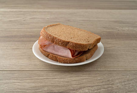 Sandwich with thin sliced ham on wheat bread on a white plate atop a table illuminated with natural light.