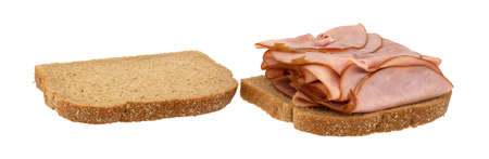Open faced sandwich with thin sliced ham on wheat bread isolated on a white background. Imagens