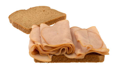 Open face sandwich with thin sliced smoked turkey on wheat bread isolated on a white background.