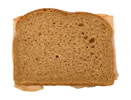 Top view of a sandwich with thin sliced smoked turkey on wheat bread isolated on a white background.