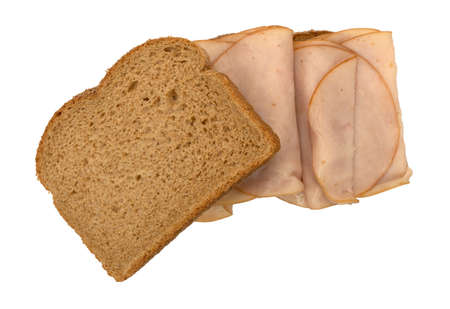 Top view of a sandwich with thin sliced smoked turkey on wheat bread with one slice to the side isolated on a white background.