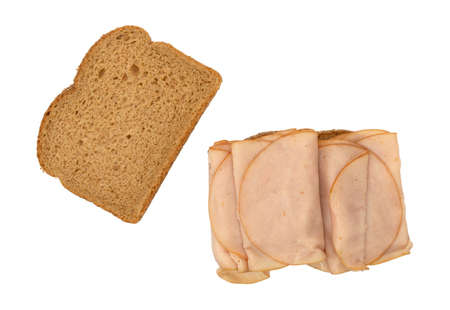 Top view of an open face sandwich with thin sliced smoked turkey on wheat bread isolated on a white background.