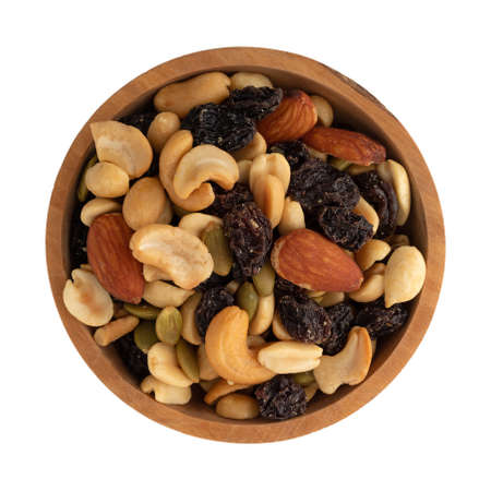 An assortment of nuts and dried fruit in a wood bowl isolated on a white background.