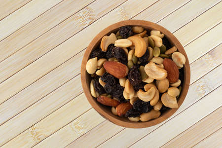 Top view of an assortment of nuts and dried fruit in a wood bowl atop a wood placemat.