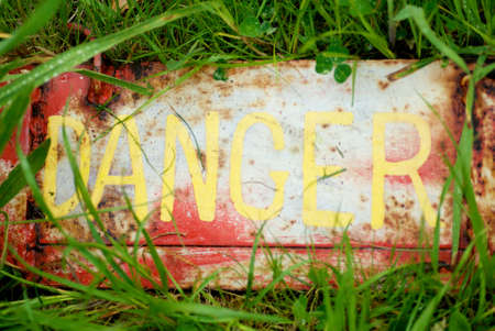 Danger sign sitting on grass with rusted look