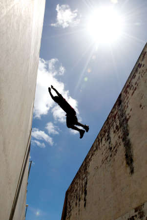 Person jumping over gap between buildings Stock Photo