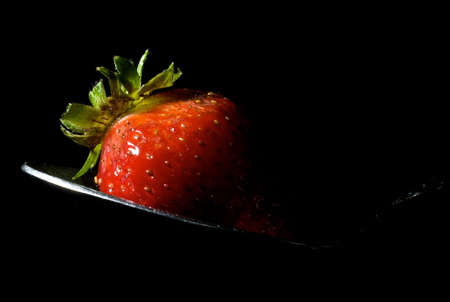 strawberry sitting on spoon with isolating black background