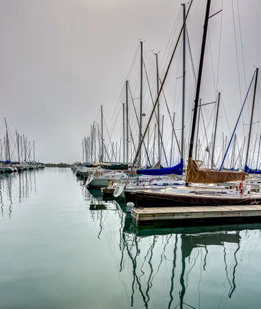 laden: Sail boats docked in the marina on a quiet fog laden morning