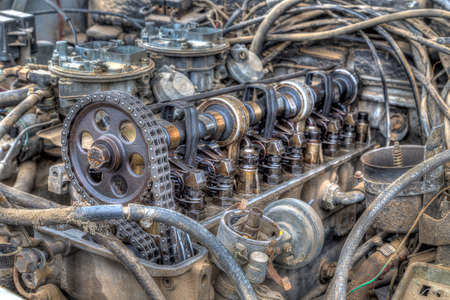 Old junkyard engine show many signs of wear and abuse with inner workings exposed Stock Photo
