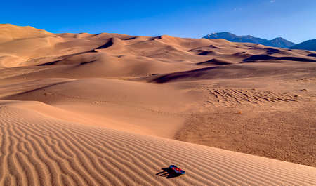 sand dune: Lone flip-flop alone on a sand dune with more dunes in the background Stock Photo