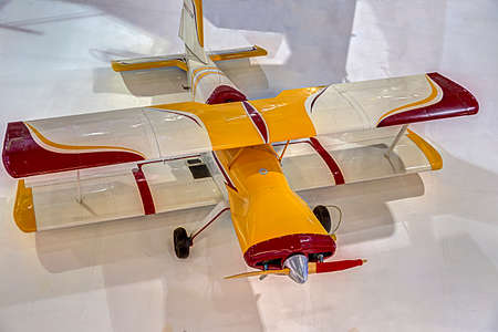 struts: Bi-plane with a wooden prop and a bright color scheme sits on the floor on a hanger