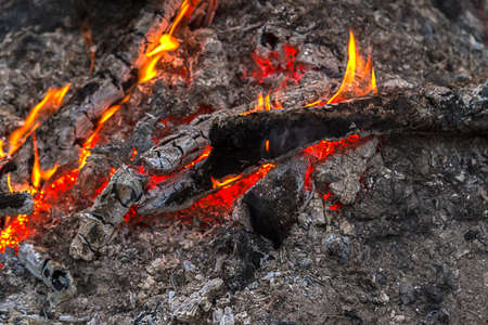 embers: Embers and flames lick at wood glowing red & orange in the night